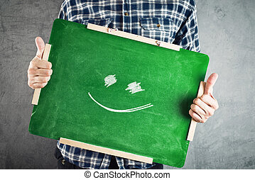 Man holding green chalkboard with smiley face