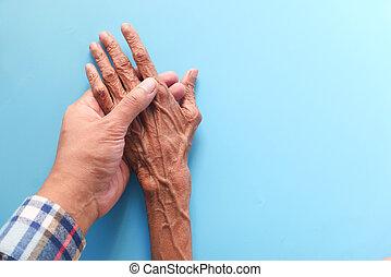 man holding hand of a senior women on blue background