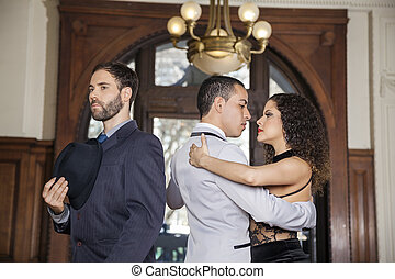 Man Holding Hat While Male And Female Dancers Performing Tango