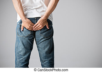 Man Holding His Bottom in Pain - Man holding his bottom in...