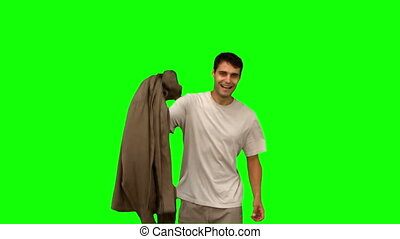 Man holding his coat on green screen in slow motion