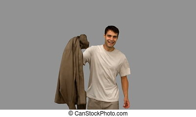 Man holding his coat on grey screen in slow motion