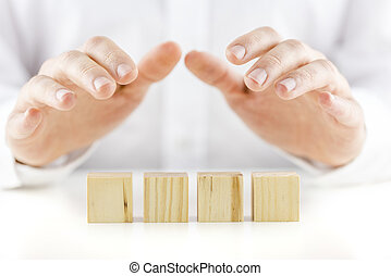 Man holding his hands protectively over a row of four blank wooden cubes on a white reflective table in a conceptual image. Ready for your text.