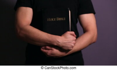 Young man holding his Bible close to his chest