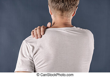 Man holding his sore shoulder trying to relieve pain on blue background. Health problems