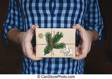 Man holding homemade wrapped Christmas Present