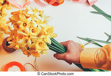 man holding in bouquet of yellow daffodils flowers and colored ribbons with rope on white background, top view