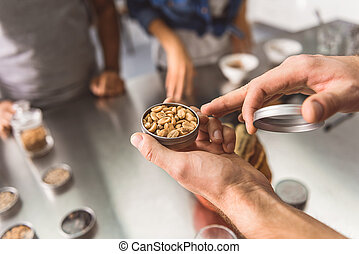 Man holding jar with coffee beans