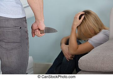 Man Holding Knife In Front Of A Frighten Woman