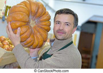 Man holding large pumpkin