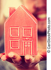 Man holding little red house, household concept