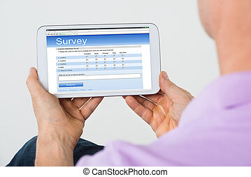 Man Holding Mobile Phone Showing Survey Form