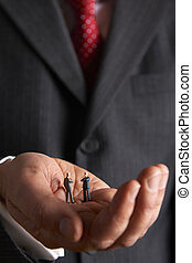 Man Holding Model Businessmen In Palm Of Hand