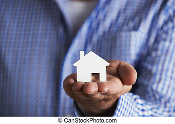 Man Holding Model House In Palm Of Hand
