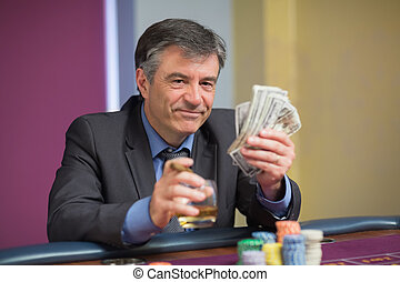 Man holding money smiling at roulette table