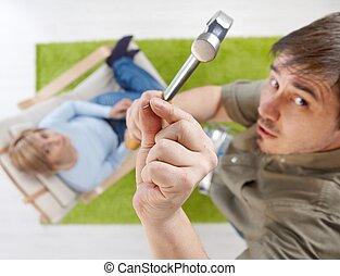 Man holding nail and hammer