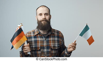 Man holding national flags - Closeup of bearded man standing...