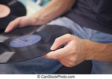 Man holding old vinyl record in his hands
