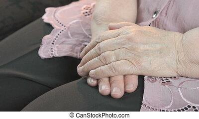 Man holding old wrinkled hands of elderly woman