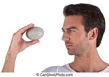 Man holding pebble in hand