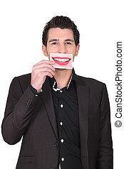 Man holding photo of lips over mouth