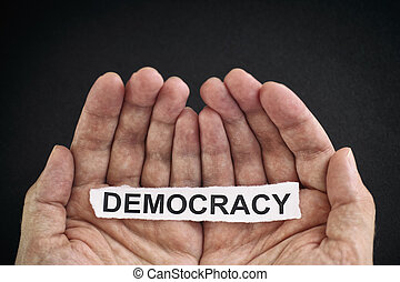 Man holding piece of paper with the word Democracy in his hands