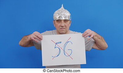 Man holding placard with no 5g sign. protesting against 5G technology and 5G-compatible antenna deployment while standing at blue background
