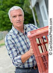 Man holding plastic crate