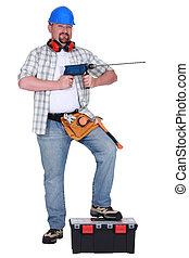 Man holding power drill and resting foot on tool box