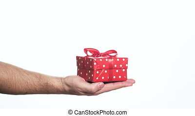 man holding red gift box in palm