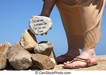 A man holds a white rock inscribed with a bible verse from John 8:7 - Let him who is without sin cast the first stone. Closeup. Focus to rock.