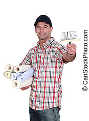 Man holding rolls of wallpaper