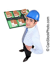 Man holding scale model of housing
