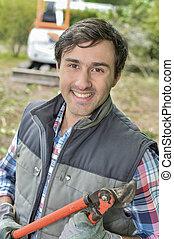 Man holding secateurs, smiling