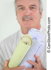 Man holding selection of wallpaper