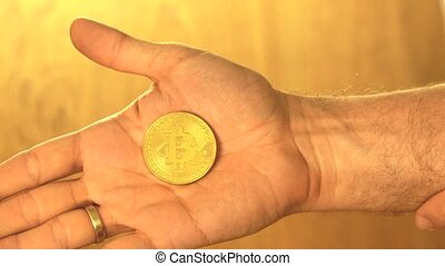 Man holding shiny golden bitcoin in his hand