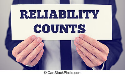 Man Holding Sign Reading Reliability Counts - Close Up of...