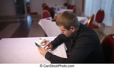 man holding smartphone browsing the internet sitting in the cafe