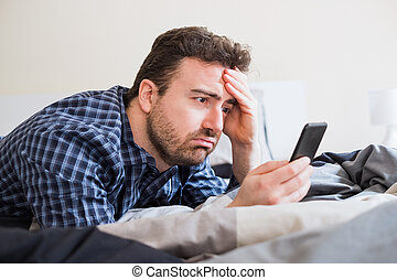 Man holding smartpohne in the bed in the morning