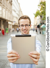 Man holding tablet computer on street