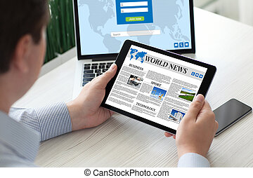 man holding tablet computer world news with notebook phone