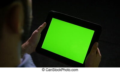 Man holding tablet pc with green screen on black background