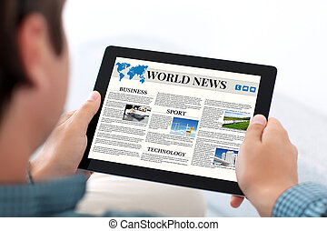 man holding tablet with world news site on a screen