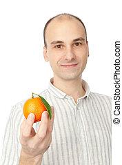 man holding tangerine