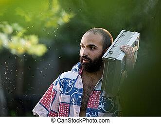 Man holding tape recorder on shoulder in park