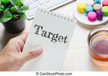 Man holding Target message on book and keyboard with a hot cup of tea, macaroon on the table.