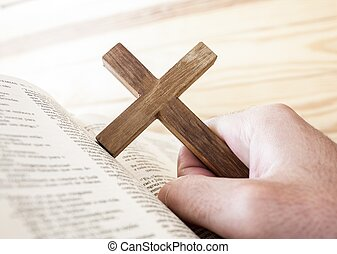 man holding the cross in the hand ,with bible under