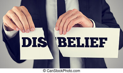 Man holding a torn paper sign in his hands with the words - Dis - Belief - spread over the two halves depicting the concept of opposites - Belief and Disbelief.