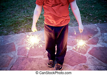 Man holding two burning fiery sparklers