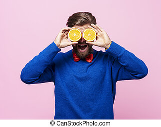 Man holding two half of orange in front of eyes